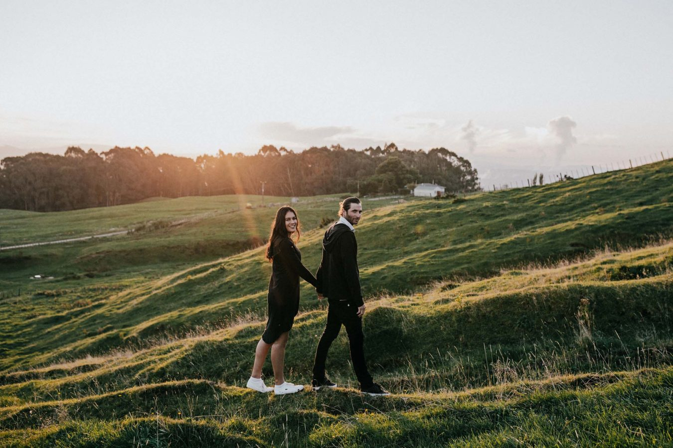couple walking along hillside in sunset