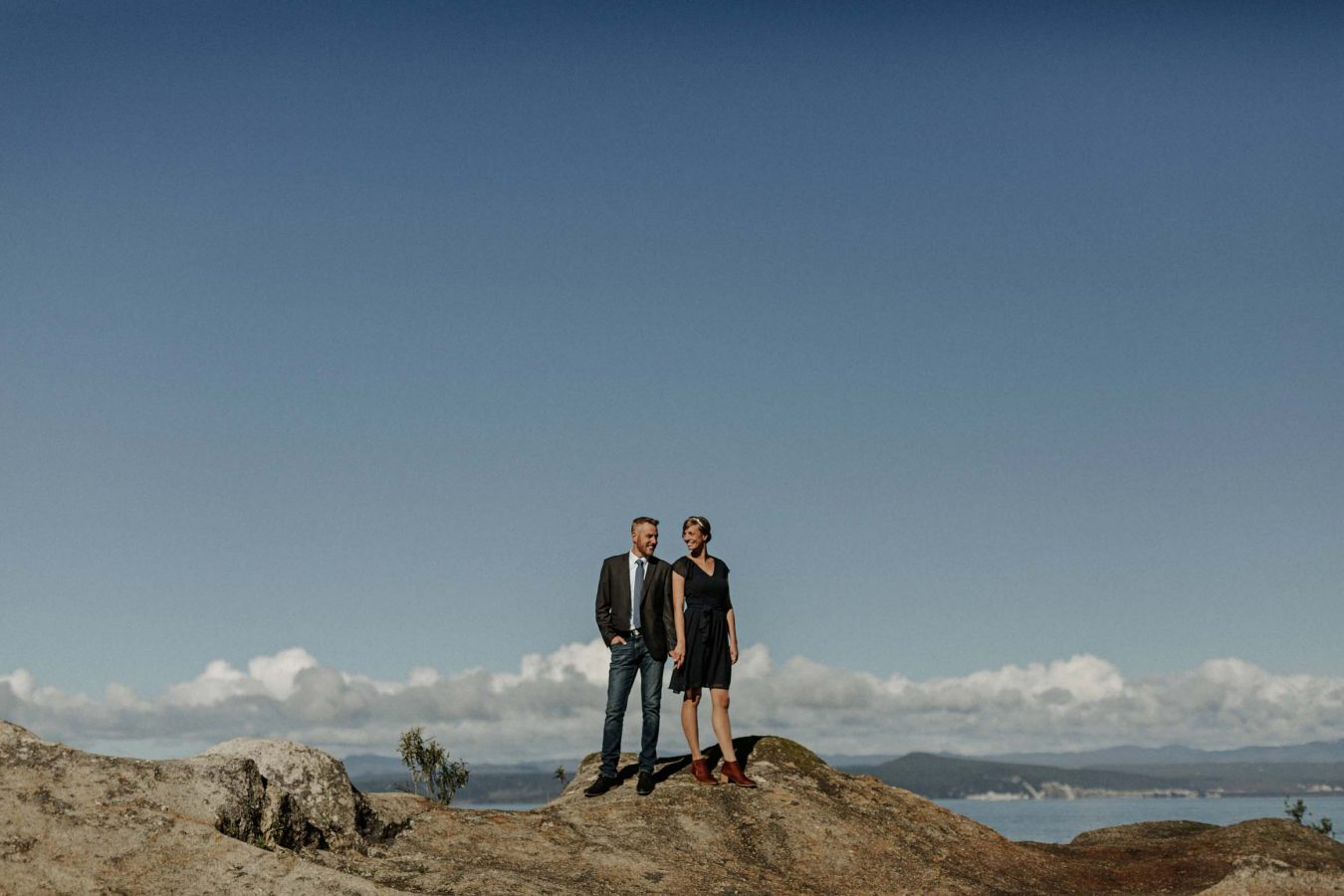 couple standing on rocks at the point in Taupo